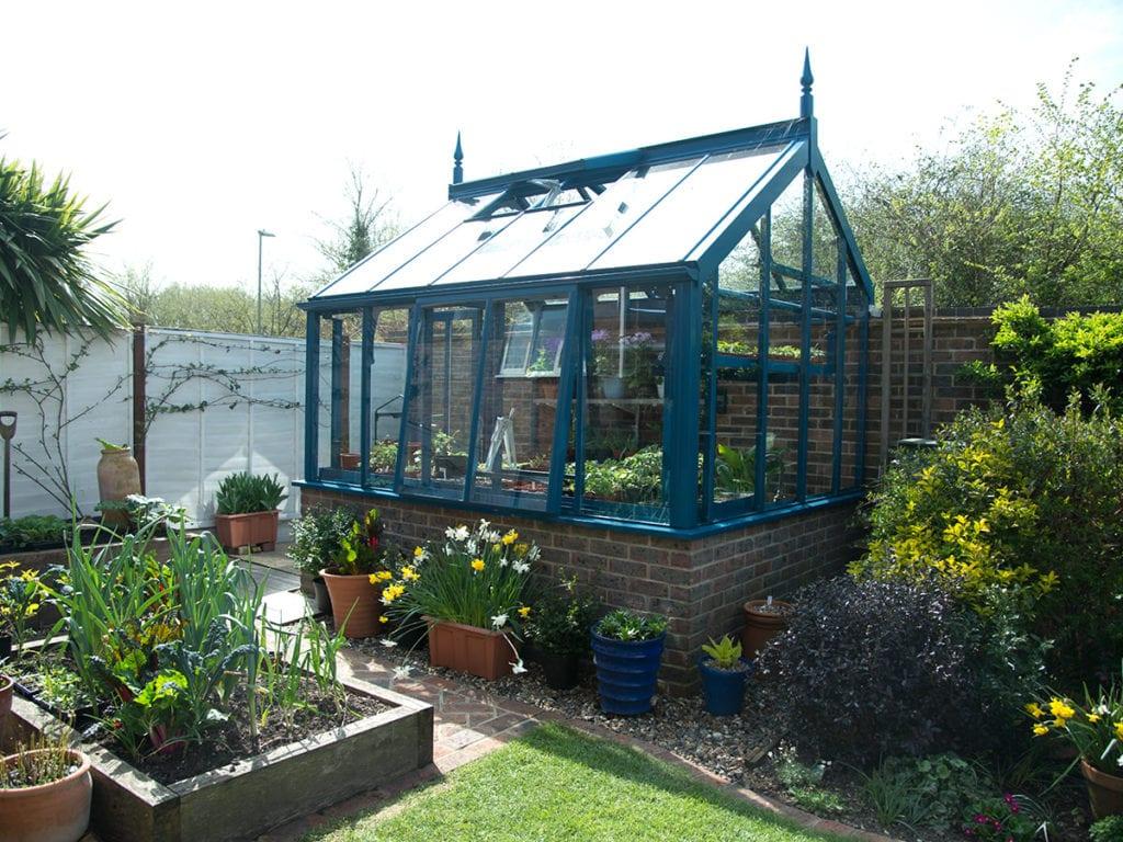 Blue three quarter span greenhouse in Hampshire garden
