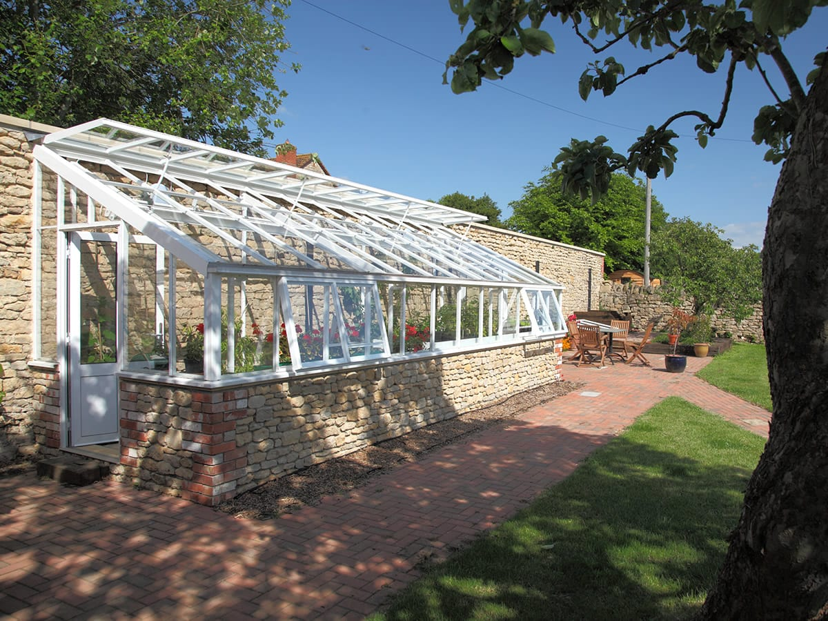 High quality bespoke lean to greenhouse with stone base